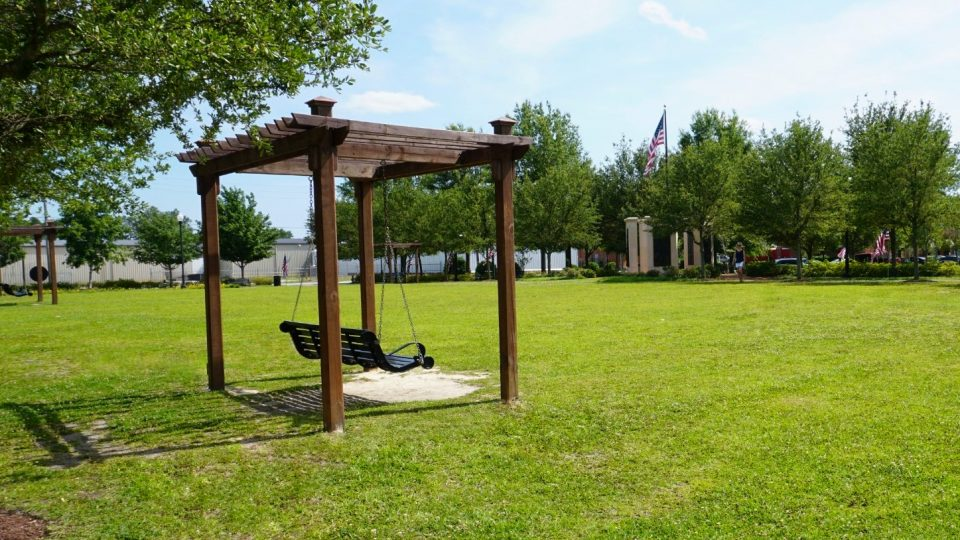 A swinging bench at Burry Park with the Veterans Memorial in the background.