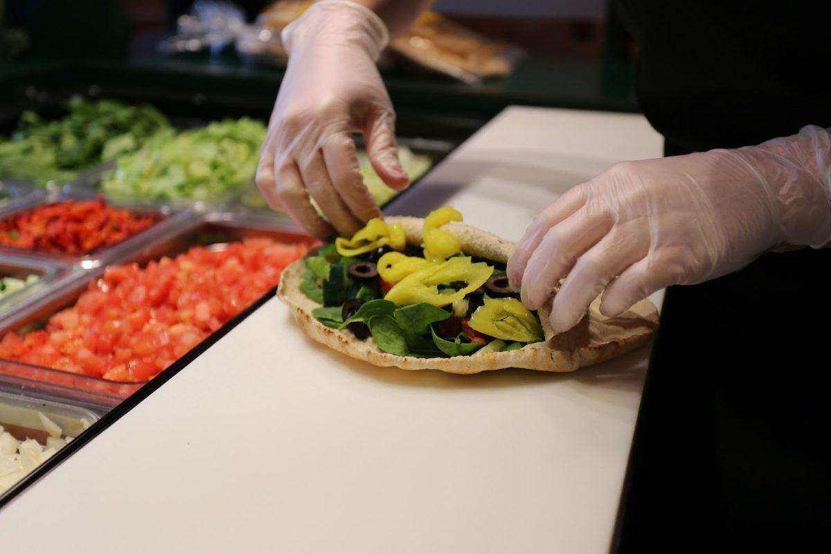 An expert pita maker prepares a sandwich at Pita Pit. image via pitapitusa.com.