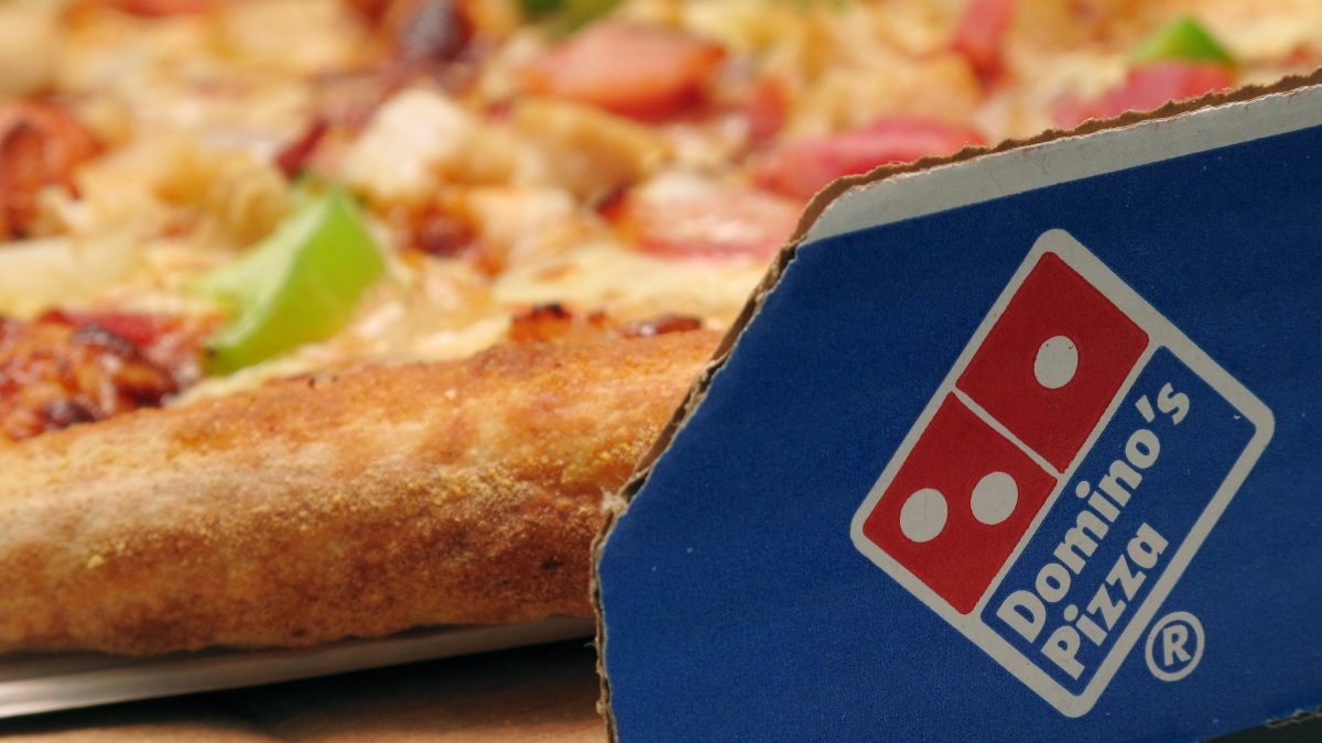 A Domino's Pizza is pictured in it's pizza box.