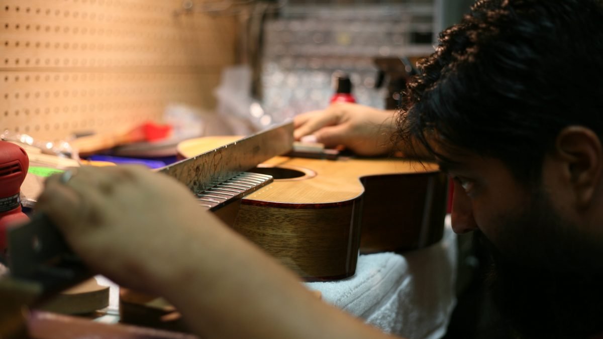 Boot, a master luthier, works on an acoustic guitar at Frets & Necks in downtown Hartsville.