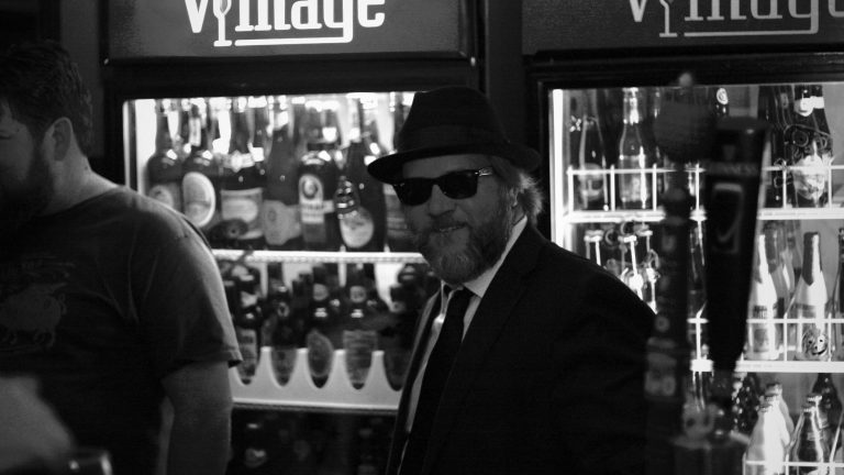 Cal, the owner of Vintage, cheeses behind the bar.