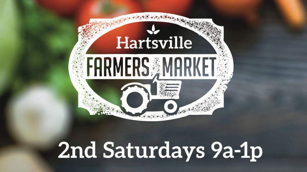 The logo for the Hartsville Farmers Market over a background of fresh vegetables.