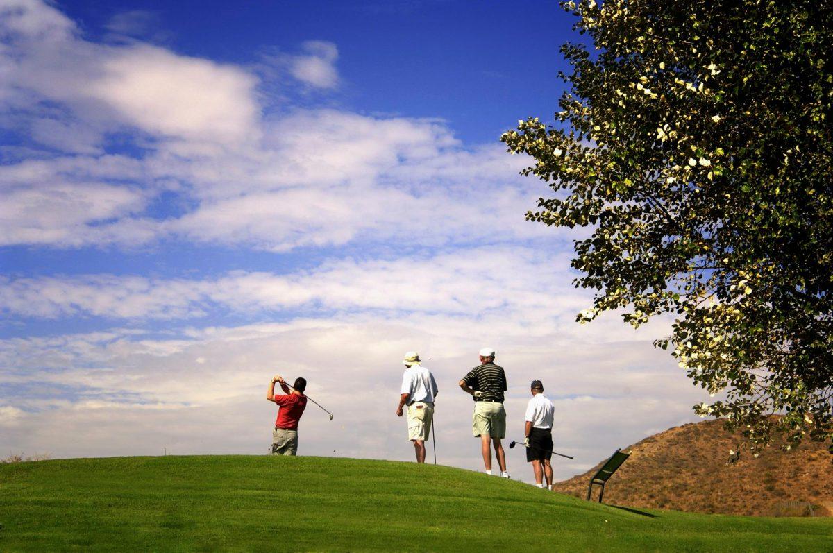 Players at Fox Creek Golf Club against a blue sky.