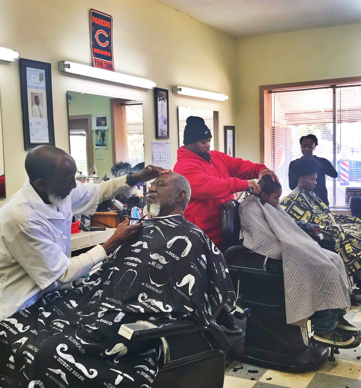 Joe and other barbers take care of clients at Roger's Barber Shop.