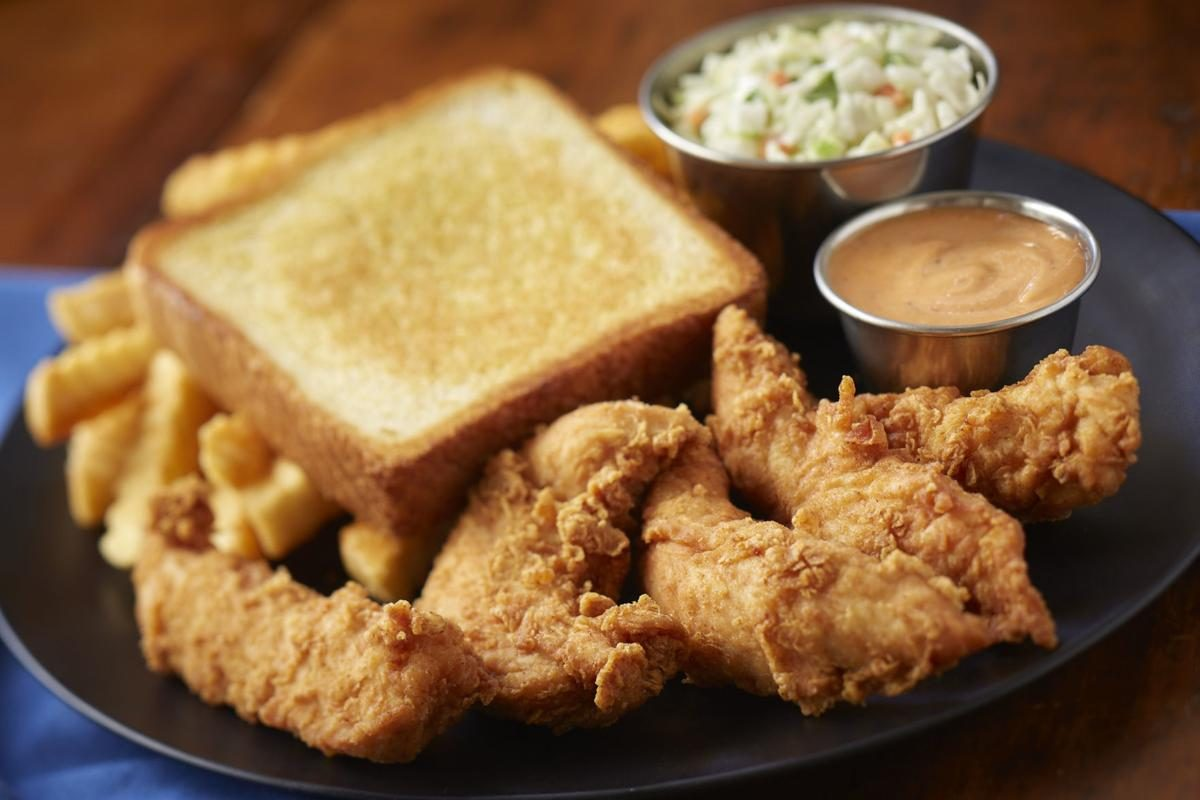 A Zaxby's chicken finger plate with slaw and toast.
