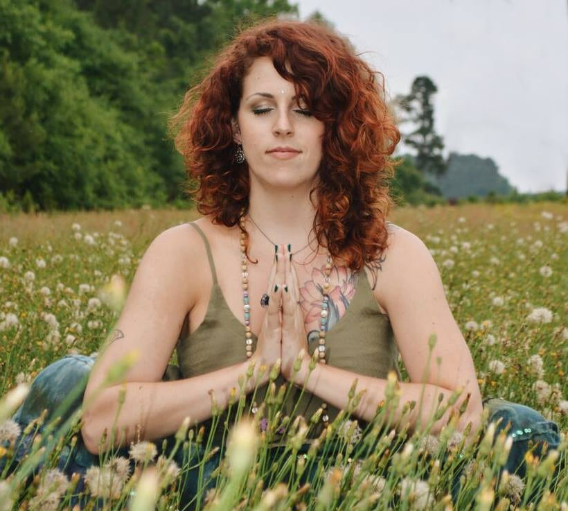 Hannah Rose in anjali mudra pose amongst wildflowers.