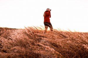 A photo of artist Madison Warner walking in a field of grass.