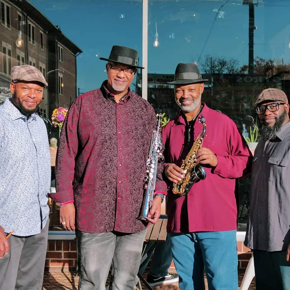 A photo of the members of The Saxxy Keys band with their instruments.