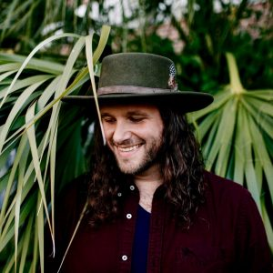 A candid portrait of Josh Gilbert in front of palm fronds and wearing a hat.