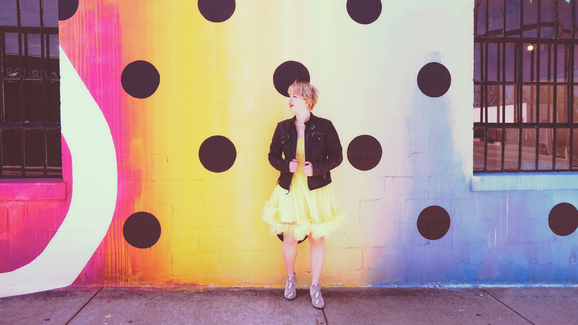 Kelly posing in front of a colorful mural.