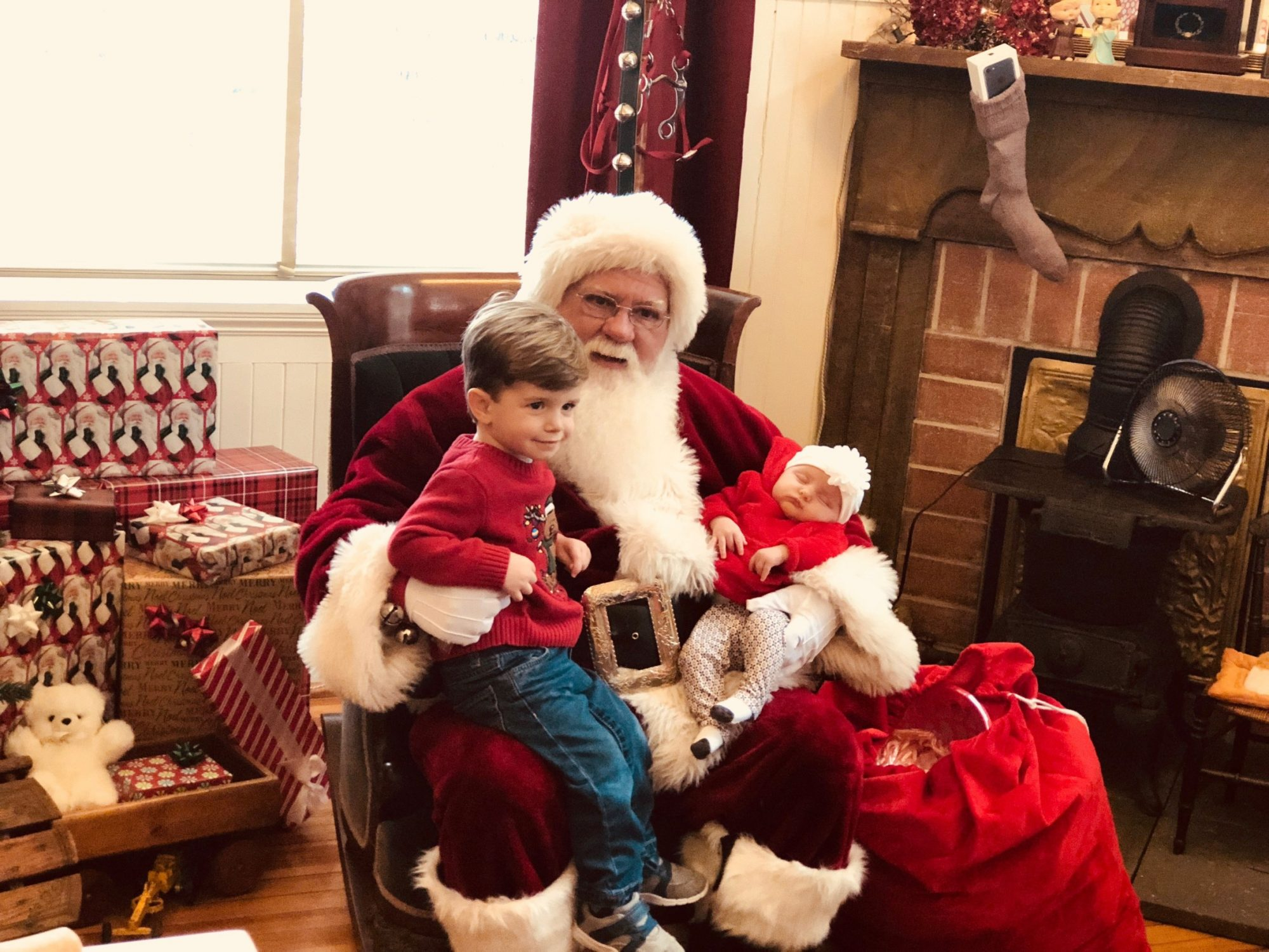 Santa Clause with a young boy in his lap.