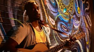 Trey Charles poses with his guitar in front a colorful mural.